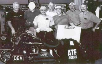 From left to right (front row): Blake Andis, Washington County Sheriff's Office (WCSO), and SA Michael Cash (DEA). From left to right (back row): Bruce Lamber, ATF RAC, unidentified agent, Sheriff Fred Newman (WCSO), Detective Chris Hazelwood (WCSO), and Captain Jack Davidson (WCSO).