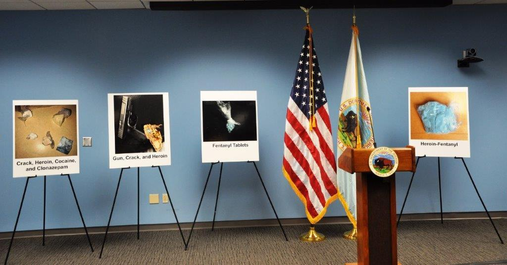 Photos of previous evidence seized in the case displayed on poster boards during press event