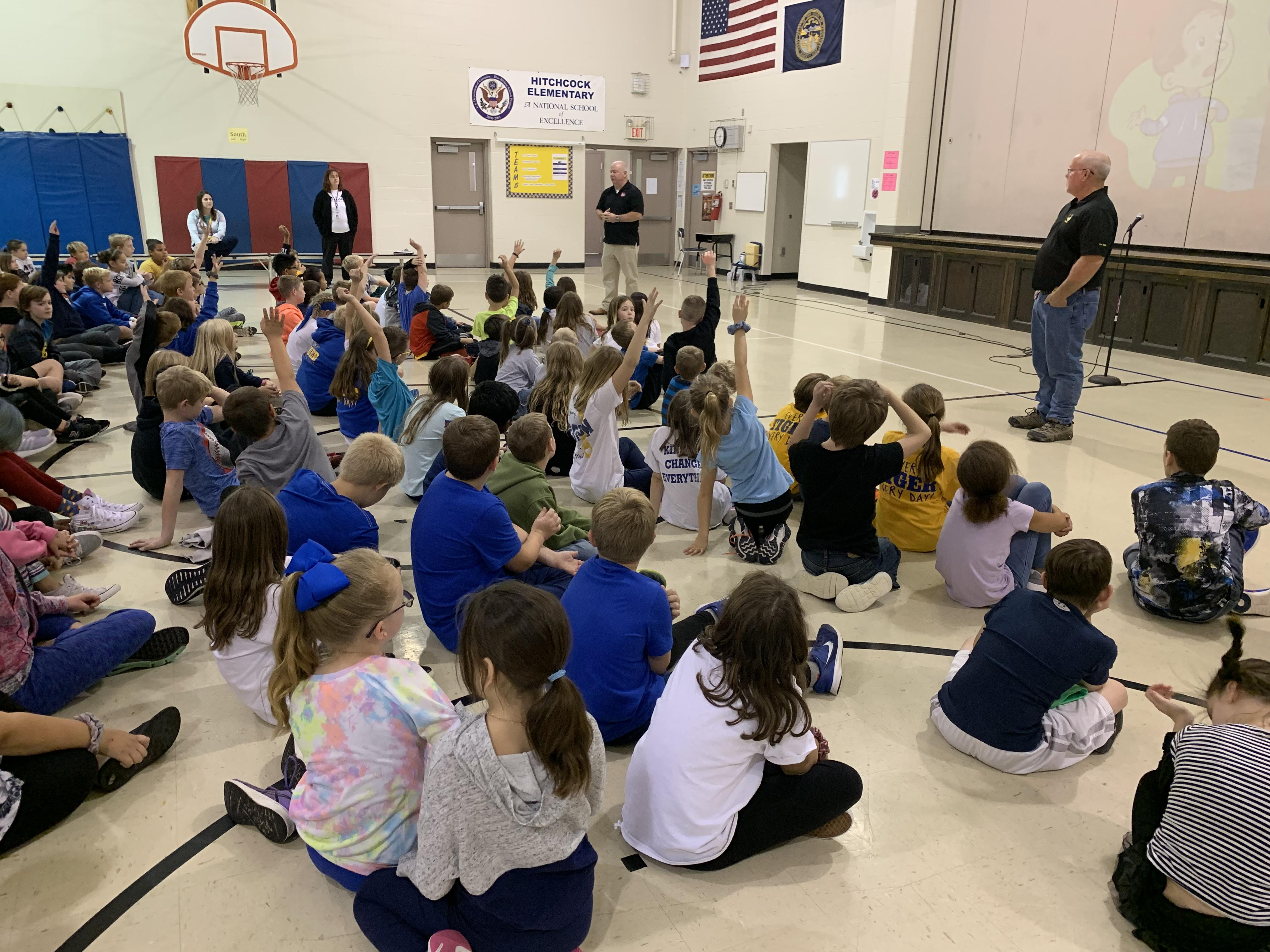 Two DEA agents answering questions at an elementary school.