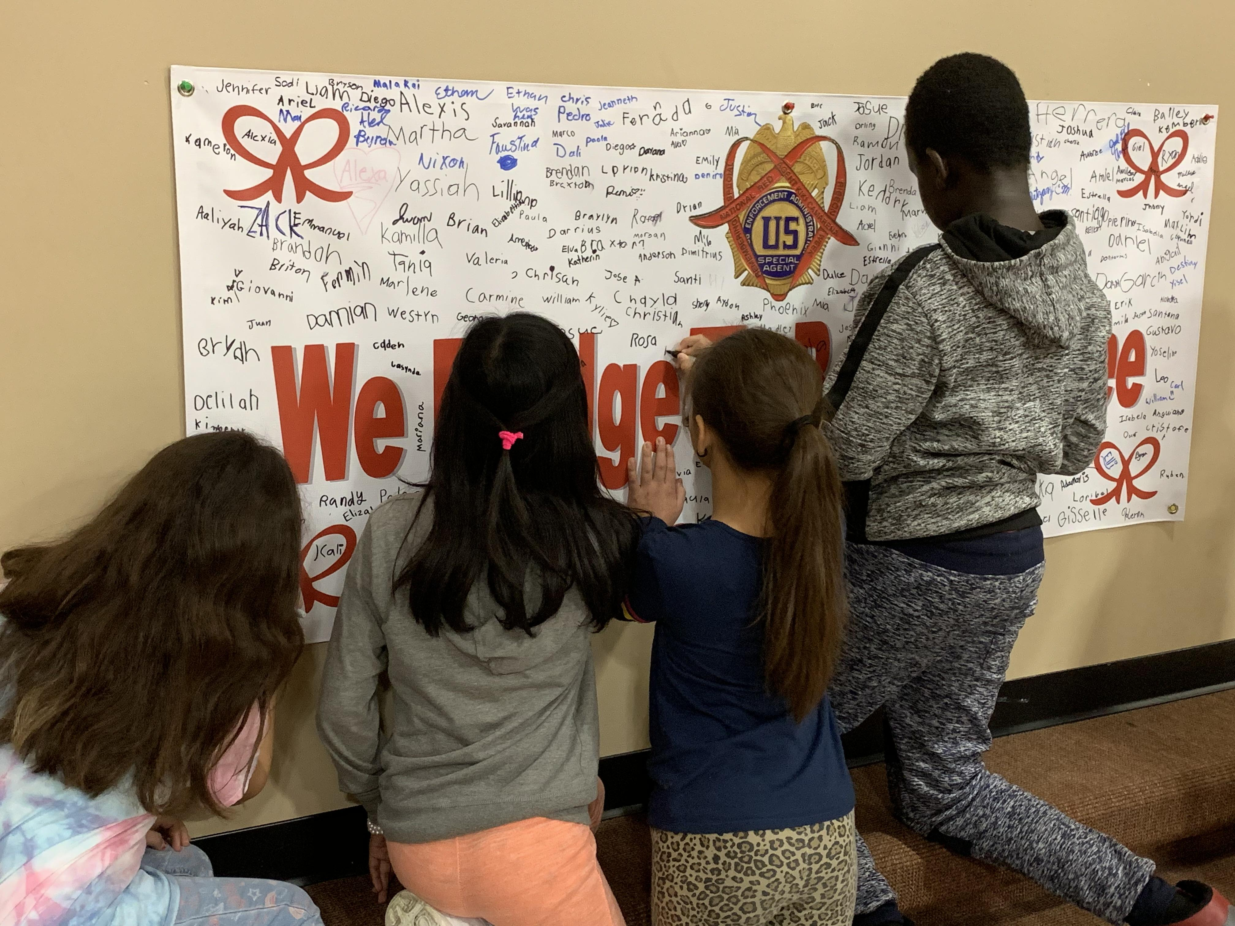 Students signing a We Pledge to be Drug Free banner.