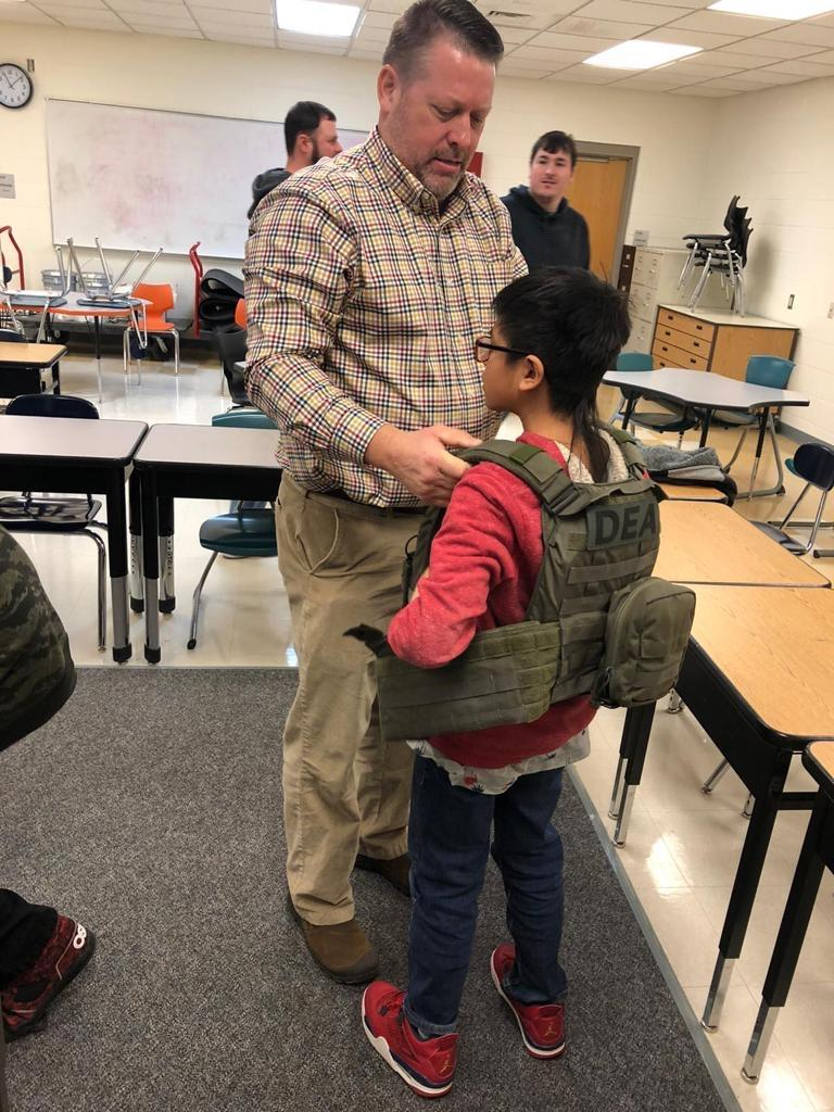 An agent with DEA helps a student try on a raid vest.