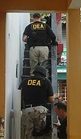 DEA special agents enter a residence in La Perla to execute an arrest warrant.