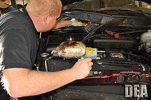 DEA Agent removing 10 pounds of meth concealed in the engine compartment of vehicle.