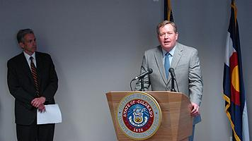 Acting Special Agent in Charge Kevin R. Merrill at the podium, and U.S. Attorney for the District of Colorado John F. Walsh.