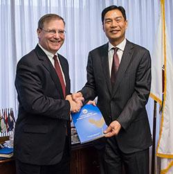 People's Republic of China Narcotics Control Bureau Director General Hu Minglang presents DEA Acting Administrator Chuck Rosenberg with his government's