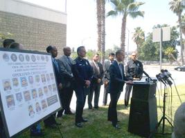 DEA ASAC Chris Evans to the right of the Operation Crystal Light Target Poster, AUSA Shawn Nelson at the podium during a press conference.