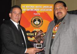 Resident Agent in Charge Reinaldo Lopez congratulating Captain James Shike III the recipient of the DEA Tribal Narcotics Officer of the Year Award.