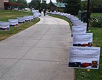 Signs displaying a photo and biography of each fallen hero lined the pathway to the park.